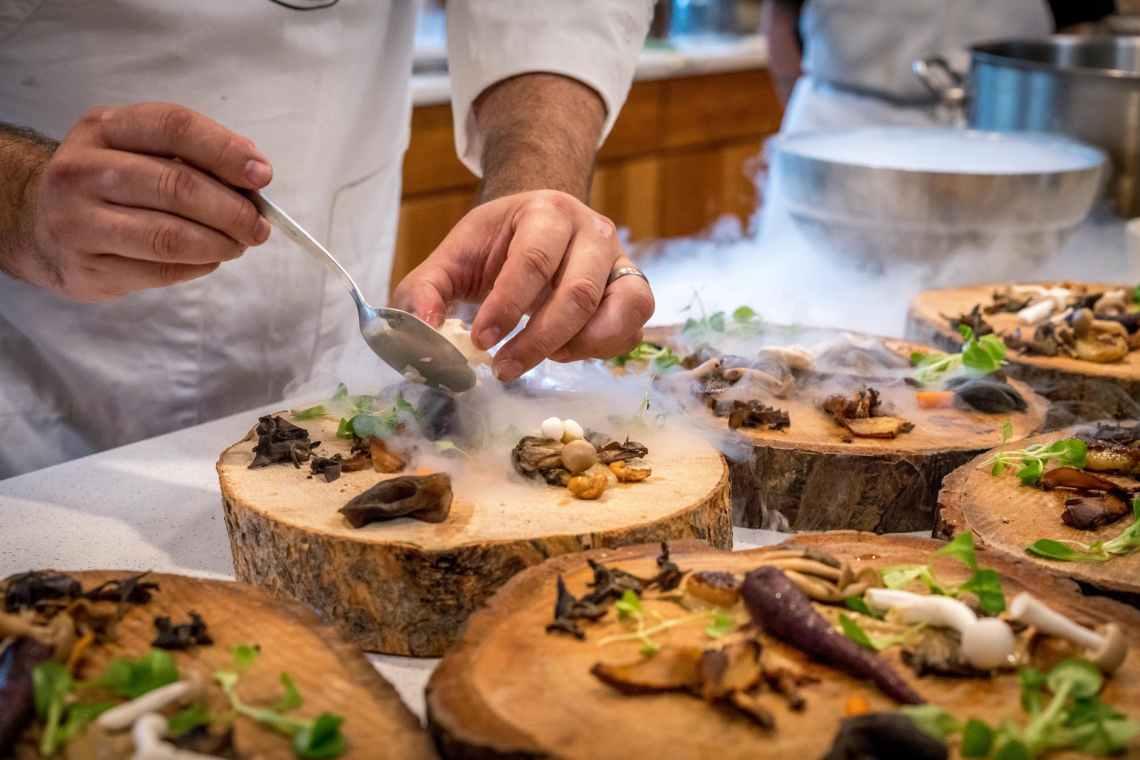chef preparing vegetable dish on tree slab