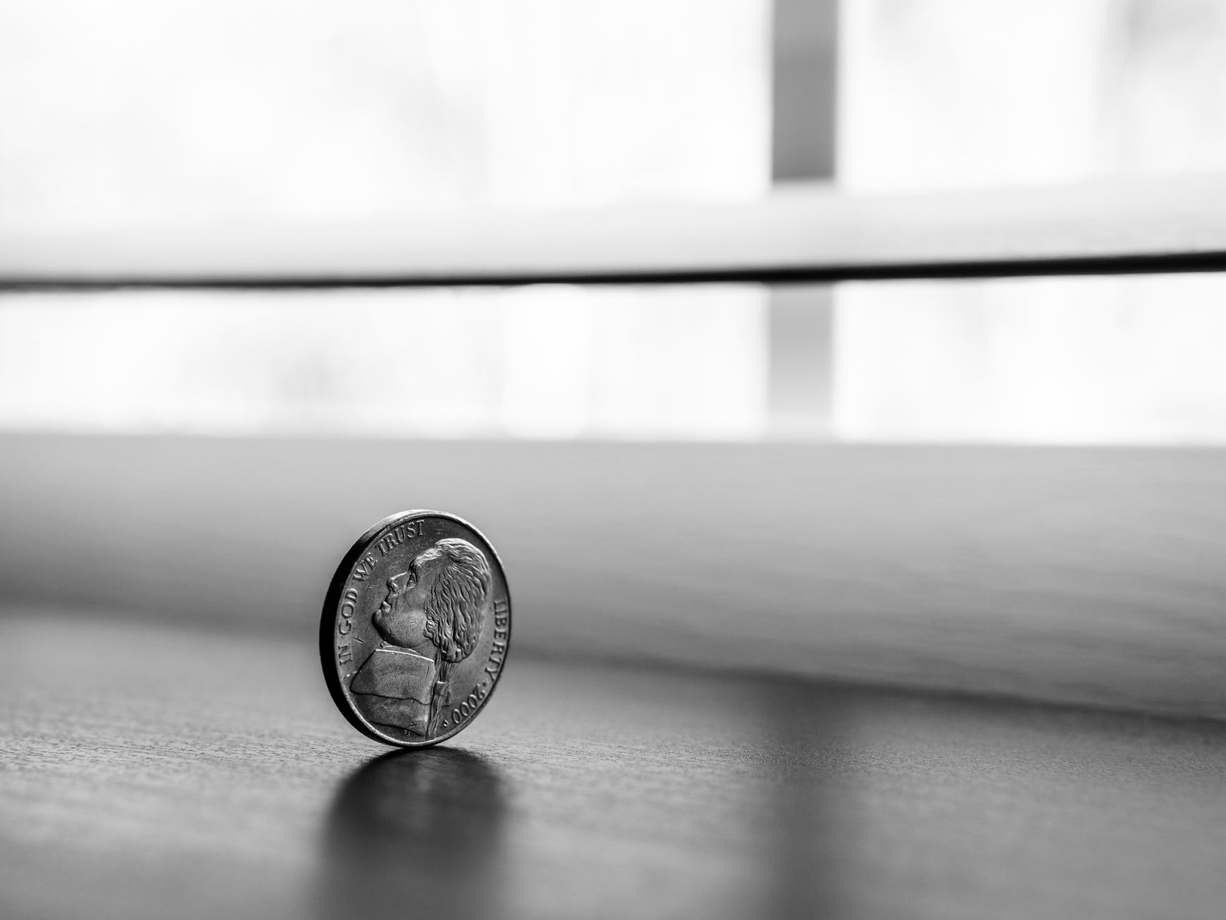 monochrome photography of round silver coin
